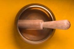 金属化碗用在一张黄色桌上的一根木棍子 库存照片
