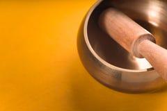 金属化碗用在一条黄色桌对角线的一根木棍子 库存照片