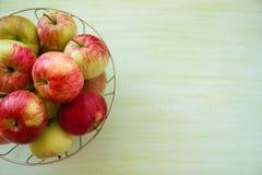 金属化碗用在左边的绿色,黄色和红色苹果在绿色木背景 免版税库存照片