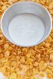 金属化碗用在被绘的白色木背景的牛奶 在一张木桌上驱散的玉米片 库存图片