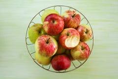 金属化碗用绿色,黄色和红色苹果和一个被咬住的苹果在绿色木背景 库存图片