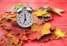 金属化站立在下落的秋天中的一张红色木桌上的时钟 库存照片