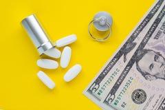 金属化药片和金钱的在黄色背景,昂贵的药物的概念,特写镜头容器 图库摄影