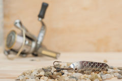 金属化诱饵,不用名字,为了渔在小石头) 与卷的木背景 钓鱼的物品 库存照片