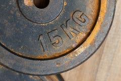 金属化重量与铁锈的15 kg在一木backgroun的长凳的 免版税库存图片