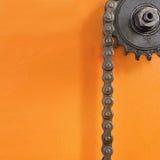 金属化钝齿轮和黑链子在橙色背景与空的空间 免版税库存照片