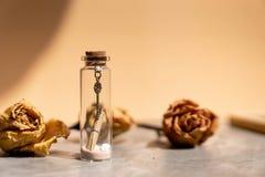 金属化钥匙、沙子和纸信件卷在玻璃瓶 库存图片