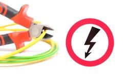 金属化钳子、绿色黄色缆绳和高压危险标志 免版税库存照片