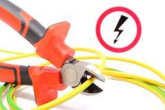 金属化钳子、绿色黄色缆绳和高压危险标志 免版税库存图片