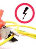 金属化钳子、绿色黄色缆绳和高压危险标志 库存图片