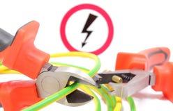 金属化钳子、绿色黄色缆绳和高压危险标志 库存照片