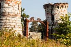 金属化门和老城堡被毁坏的塔  免版税图库摄影