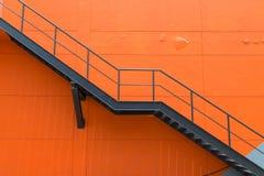 金属化防火梯或紧急出口在Buliding橙色墙壁上  库存照片