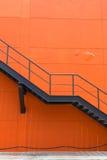 金属化防火梯或紧急出口在Buliding橙色墙壁上  免版税库存照片
