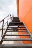 金属化防火梯或紧急出口在Buliding橙色墙壁上  库存图片