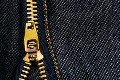金属化openning在与拷贝空间的蓝色牛仔裤纹理的拉链 免版税库存图片