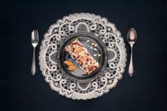 金属古色古香的板材、匙子和叉子,在一块老餐巾在黑背景 库存照片