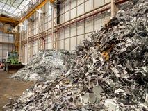 金属和铝废弃堆,并且打瞌睡的人回收工厂 库存照片