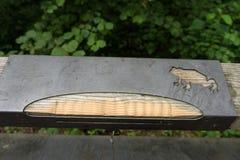 金属在木路轨的青蛙雕塑 免版税图库摄影