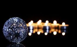 金属在茶蜡烛前面的圣诞节球 免版税库存照片