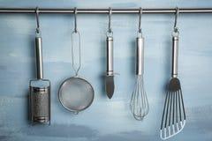 金属垂悬在机架的厨房器物 免版税库存照片