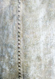 金属垂直的空白的背景与铆钉的击倒一边 库存图片