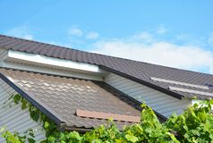 金属屋顶建筑问题范围 屋顶建筑的山墙和谷类型有塑料下端背面和招牌的 库存照片