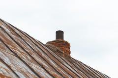 金属屋顶,油漆几乎消失了 在她的烟囱上 喇叭和kerpich 免版税库存照片