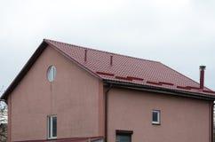 金属屋顶建筑 雨天沟和雪卫兵 同轴的烟囱 有单独热化的议院 库存图片