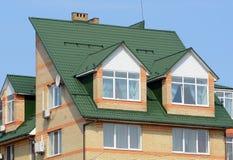 金属屋顶 雨天沟和顶楼有双重斜坡屋顶的房屋窗口 屋顶建筑 免版税图库摄影