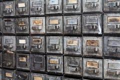 金属抽屉 闭合的档案存贮,档案橱柜内部 有索引卡片的年迈的银色金属箱子 图书馆 免版税库存照片