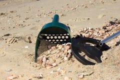 金属探测器和沙子瓢在一个晴朗的海滩 库存照片
