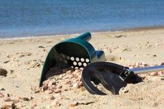 金属探测器和沙子瓢在一个晴朗的海滩 免版税库存照片