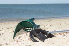 金属探测器和沙子瓢在一个晴朗的海滩 库存图片