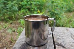 金属杯子在木桌上的咖啡 免版税库存图片