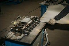 金属板料在工作者手,金属工艺设备工具上在工业工厂 免版税库存照片