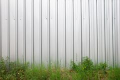 金属板有绿草和植物的屋顶或钢片屋顶 免版税库存照片