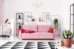 金属架子和抽象绘画在粉末桃红色长沙发后在典雅的白色客厅 库存图片
