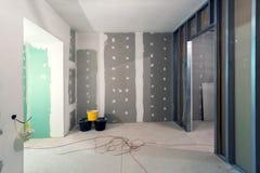 金属框架和石膏板干式墙石膏墙壁、三个桶和电导线的在公寓建设中 库存照片