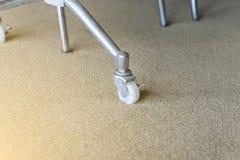 金属桌的肮脏的橡胶轮子在地毯的 库存图片