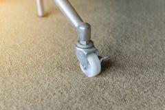 金属桌的肮脏的橡胶轮子在地毯的 图库摄影