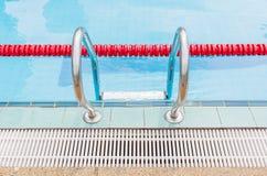金属梯子关闭与游泳poo红色明显的车道  库存照片