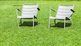金属椅子在新鲜的草站立在夏天公园 库存图片