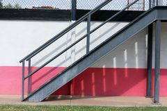 金属楼梯对有一个铁丝网的白色和桃红色墙壁在上面 库存照片