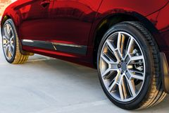 金属汽车的徽标不是没有噪声油漆显示的副纹理视图 一辆现代红色汽车的轮胎和合金轮子在地面上的在日落 汽车外部细节 免版税库存图片