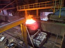 金属熔炼在大铸造厂 在一棵冶金植物的铁和钢铁生产 钢铁工人 冶金学过程 免版税库存照片
