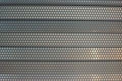 金属片与在平行的水平的金属的圆孔蒙蔽背景纹理 免版税库存图片