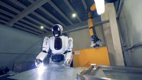 金属片由一种现代工厂设施的一个靠机械装置维持生命的人焊接 股票视频