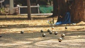 金属球和橙色木球在地面在家庭菜园-演奏上Petanque在一个晴天 库存照片