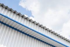 金属白色板料和蓝色角落的工业建筑 顶房顶金属板或工厂厂房波纹状的屋顶  免版税库存照片
